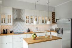 Na ścianie między blatem roboczym a szafkami wiszącymi w kuchni ułożono prostokątne płytki, we wzór jodełki.
