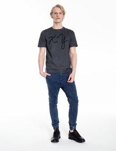 Model is wearing: XY chromosomes t-shirt in grey & blue denim Universum jeans