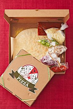 Delight a neighbor or friend with a make-at-home dinner for the evening. Use our recipes for pizza dough and sauce and tie up bundles of classic pizza toppings. To package this creative gift, use a pizza box and stick on a cute custom label. #diychristmasgift #diygift #homemadechristmasgifts #easydiygifts #bhg