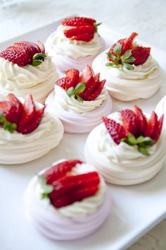 Whipped cream and a sliced strawberry on a meringue