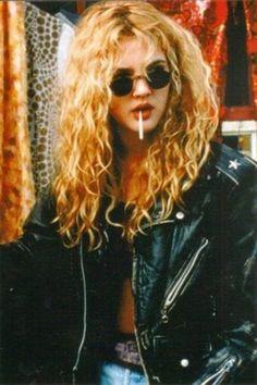 Glastonbury Festival Fashion Inspiration. 90s, black leather biker jacket, blonde curly hair, blue denim, sunglasses, cigarette, smoking