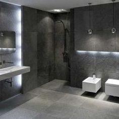 Aranżacje z płytek - łazienki i pokoje kąpielowe. Łazienka w modnych szarościach z płytka gresową strukturalną. Geometryczna ceramika łazienkowa podkreśla nowoczesny charakter wnętrza. Ekspozycja w salonie w Krakowie.