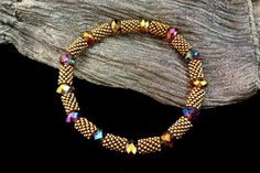 "This elastic bangle, the Venice, features dark amethyst fire-polished crystals alternating with tubes of dark bronze Miyuki seed beads woven in peyote stitch. This beaded elastic bracelet slips easily onto the hand without the bother of a clasp. The particular stretch bracelet pictured measures 7"" once it is on the wrist, but it can easily be customized to fit anyone. (photo only)"