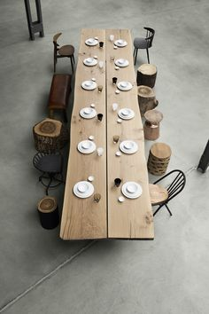 Long wooden table with logs as a stool and various .- Langer Holztisch mit Holzstämmen als Hocker und verschiedenen Stühlen Long wooden table with logs as a stool and various chairs -