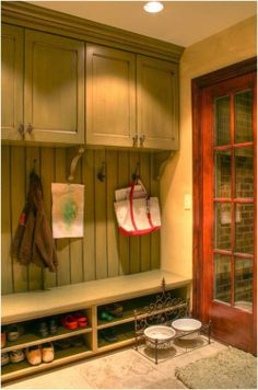 Great ideas for storing stuff in a mudroom or entry foyer... use wall cabinets placed higher than normal, and build a row of low shelves for storing footwear. Kids can sit on the shelf and take off their shoes.