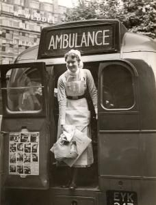 A nurse stands in the open rear emergency exit doorway of a T-type Green Line coach (No T216) which has been converted into an ambulance. The coach was used to evacuate patients and staff from Westminster Hospital, prior to the outbreak of the Second World war. A poster on the inside of the door has a series of photographs documenting the evacuation. Unknown photographer, 1 Sep 1939