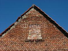 Aus rotbraunem Ziegelstein gemauerter Giebel mit zugemauertem Fenster in Helpup bei Oerlinghausen in Ostwestfalen-Lippe am Teutoburger Wald