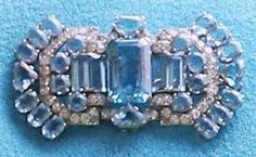 The Queen Mother`s Art-Deco Aquamarine brooch, now worn by The Queen. This brooch mostly worn by the Queen Mother in her earlier years. It contains multiple cuts of aquamarine jewels with diamond accents.