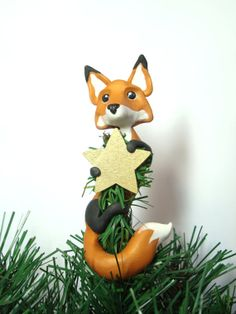 Custom Fox Christmas Tree Topper by LittleBerties on Etsy, £30.00. $49.95 USD/ +$9.99 US shipping. This ornament is handmade in an orange coloured blend of polymer clay which has a subtle golden shimmer that gently sparkles where the light catches it, holding a little hand painted wooden star. Foxes measure approx. 5 inches long and 1.5 inches wide. Please select when purchasing whether you would prefer a gold or silver star.