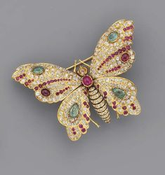 AN ANTIQUE GEM-SET AND DIAMOND BUTTERFLY BROOCH The diamond and black enamel striped abdomen with ruby thorax, brown diamond head and ruby eyes, to the old-cut diamond wings set en tremblant with cabochon ruby and emerald detail, mounted in gold, circa 1880