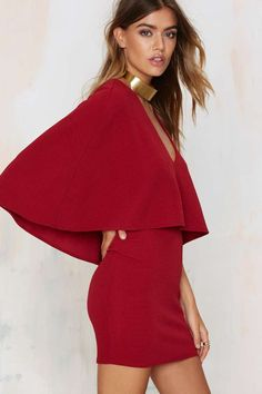 This stunner is burgundy and features a cape overlay, mini silhouette, and textured fabric.