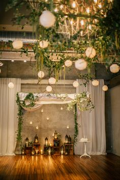 """Vines, branches, and candles suspend from the ceiling's beams to create a """"floating"""" chuppah. The result is a bewitching, whimsical atmosphere that beautifully juxtaposes with an edgy urban industrial setting."""