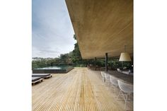The living room opens onto a large deck with a raised swimming pool. The sun-loungers are InOut by Gervasoni.
