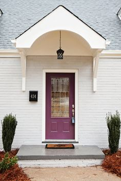 Portico added to 1950's cape cod. Blackberry by Sherwin Williams on the new door.