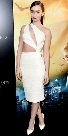 LILY COLLINS At the Mortal Instruments: City of Bones premiere, Lily Collins kicked it up a notch in a sexy white Cushnie et Ochs midi dress with dramatic cut-outs that exposed skin in all the right area, pairing it with white Giuseppe Zanotti pumps.