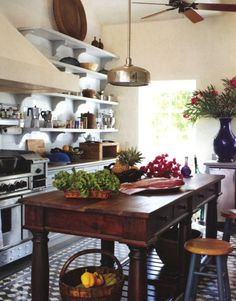 Rustic table used in kitchen for an island. Genevieve Faure. Architectural Digest.
