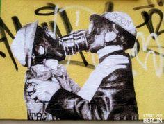 Kissing gas masked protester graffiti.  Street art Berlin