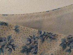 Working from the right side of the lining, sew about 1/8″ to 1/4″ away from the seamline catching in the seam allowance underneath. Press the seam edge flat with the lining on the inside of the garment.