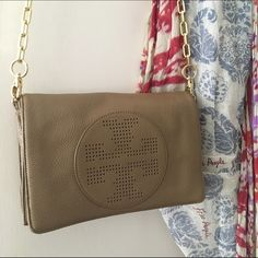 Tory Burch cross body purse Original Tory Burch purse, can include dust bag. This was used once but in great condition! The back side has a large pocket. The inside is roomy with one zippered pocket, one open pocket, two card holder slots, and a gold logo. The flap is magnetic closure and strap is gold as well. There is a tiny make up speck on the inside flap, but nothing noticable. Let me know if you want to see anymore photos! Tory Burch Bags Crossbody Bags