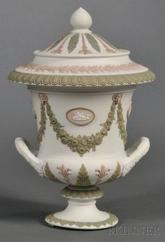 Wedgwood Three-Color Jasper Vase and Cover, England, 19th century, upturned loop handles, white ground with green and lilac floral festoons, medallions and acanthus leaves, the festoons terminating at ram's heads.