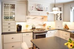 A kitchen remodel in Centerpoint, New York swapped a kitchen and a dining room to make whole new space. Designer Phoebe Steinhoff-Smith used Fieldstone Cabinetry's Rockingham inset door style in Maple finished in a white cabinet color called Macadamia with Nickel glaze to bring brightness into the room. The Nickel glaze complements the gray cabinet color of the island, Driftwood. Phoebe is a designer for Coastal Cabinet Works, a Fieldstone Cabinetry dealer in Plainview, New York.