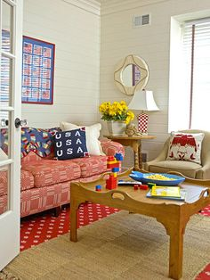 Relaxation Central The homeowners' five children love to relax in this homey TV/playroom. Neutral paneling and a natural fiber area rug adds texture to the space. The bold red sofa and crimson carpet combine with patriotic accessories in shades of blue and white. An oversized wooden table can hold snacks, books, or toys.