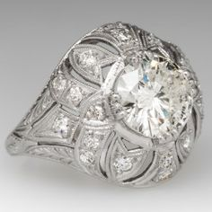 This stunning 1920's domed platinum ring features lovely milgrain accents and wheat motif engravings. The center diamond is a more modern round brilliant diamond weighing 2.55 carats. The diamond has gorgeous sparkle and fits perfectly in this setting for a fantastic look! The ring is accented with 20 additional round diamonds for all over sparkle. The condition is incredible and it's ready for another lifetime of wear. One of our new arrivals that we couldn't wait to share, ...