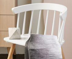 Licht & Lucht: Vormentaal en kleur maken dit tot een actueel interieur. Het bleke roze neutrale hout met de witte spijlenstoel verraden het Scandinavische design. De lap stof met penkras dessin is van Ferm Living.