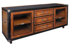 Royal Navy Console Authentic Models Inspired by classic Royal Navy furniture. Made from warm wood finished with bronze hardware like heavy duty box-lifts and solid bronze corners that practically guarantee a quality that will span generations. Finished in rich honey and French sky-black lacquer. The substantial piece moves easily on wood wheels bracketed in brass finished steel, that lock when stationery.