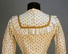 PRINTED COTTON POLONAISE DRESS, 1880's. Cream with repeat of brown grape clusters, unboned pannier bodice with pleated ruffle to yoke and cuff, brown trim bands, back buttons, lace hem trim, under skirt with double row of hem pleats. B-38, W-26, bodice L-48, underskirt L-42.
