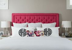 Glam bedroom features hot pink, tufted headboard on queen bed dressed in silver polka dot bedding and monogrammed shams as well as floral lumbar pillow flanked by white nightstands with brass pulls topped with stacked glass lamps.
