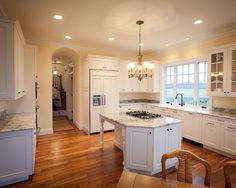 Dark floors, recessed lighting and stove on center island.  Where is the range hood? Like this kitchen...spacious.