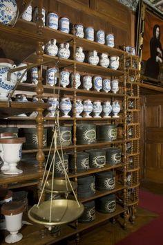 Détails mobilier pharmacie avec dressoirs, colonettes, albarelli, pilluliers, chevrettes, pots-canons et bouteilles en faïence
