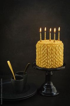 Golden birthday cake with knitted pattern made of fondant and candles on a cake stand