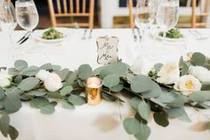 Courtney Inghram Events and Floral Design picture by Alisandra Photography based in Virginia. Trump Winery wedding with silver dollar eucalyptus table garland with white garden roses and mercury glass gold votives.  White and greenery wedding flowers for organic, natural vineyard wedding.