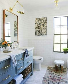 vintage bathroom with blue vanity and gold hardware details