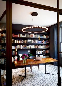 An elegant office space that reads like an old-fashioned library, thanks to the wall-spanning bookshelves and exposed-bulb chandelier.