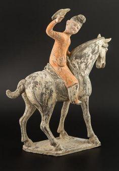 Fauconnier assis sur un cheval à l'arrêt, bouche ouverte. Le buste tourné vers la droite, l'homme regarde le faucon posé sur sa main. H: 44 cm, L: 38 cm. Terre cuite sous engobe à rehauts de polychromie. Dynastie Tang (618-907). Test de thermoluminescence. Prov.: Coll. espagnole.