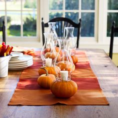 fall decorations - mini pumpkins, candles, hurricane lamps, orange and red runner