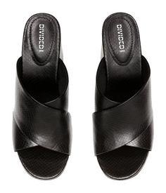 Svart. Ett par slip in-sandaletter i präglad läderimitation. Sandaletterna har öppen tå och klädd blockklack. Foder och innersula i läder. Yttersula i gummi