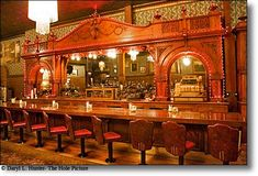 Irma Hotel~ Cody WY   The beautiful cherry wood back bar, one of the most photographed spots in town, was given to Buffalo Bill by the Queen of England in 1900 at which time manufacturing cost of this magnificent example of wordworking craftsmanship was $100,000, is now worth in excess of one million dollars.