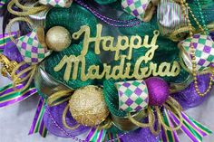wreath Mardi Gras, Mardi Gras wreath, Mardi Gras door, Mardi Gras decorations, purple gold green, wreaths, front door wreath  If you like all the bling, glitz and bright colors of Mardi Gras then you are going to love this green and purple deco mesh wreath. This wreath has it all with a feathered and sequin mask, Happy Mardi Gras sign, beads, glittered balls, two gold and one purple, gold, and green Fleur-De-Lis, and glittered ribbon. This wreath from tip to tip is 31 inches across and about…