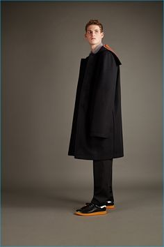 Raf Simons black wool overcoat, extra big long sleeved shirt, and pinstripe trousers with Adidas by Raf Simons Stan Smith sneakers.