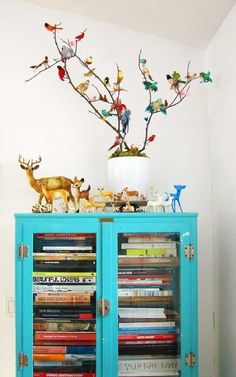 Boho / Eclectic bright blue painted cabinet, and a flock of colorful birds displayed on natural twigs! I love it, so cheerful!