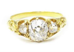 This darling diamond ring comes to us from the late Victorian era, and is an absolute confection of 18k yellow gold and diamonds. Three glittering stones are set low in a beautifully carved mounting with sophisticated scrollwork shoulders. The center diamond weighs in at 0.79 carats and is H color, SI1 clarity. Total diamond carat weight of the ring is 1.03 cts.