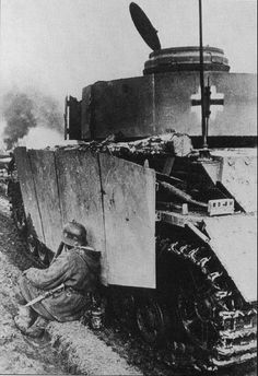 A weary German soldier takes a rest under cover of a PzKpfw IV as the war rages in the distance