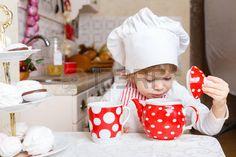 Kleines Mädchen in Schürze und Kappe der Koch mit süßen Desserts sitzt am Esstisch in der Küche im Haus. Helfer Mutter. 2 Jahre alt. Lizenzfreie Bilder