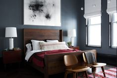In Coldplay guitarist Jonny Buckland's master bedroom, the bed by BDDW is dressed with linens by Ralph Lauren Home and a pillow covered in a vintage grain sack; the chairs are by Eames, the painting is by Thilo Heinzmann, and the walls are painted in Farrow & Ball Modern Emulsion in Down Pipe. Tour the rest of the home here.