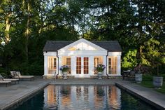 Traditional pool house in white with gray shingled roof [Design: Northworks…