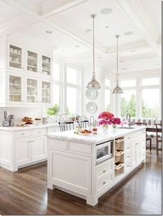 Love this look - white on white, glass front cabs, white/gray counters, industrial fixtures.